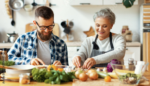 Fotografering Happy mature woman with adult son cooking together at home.