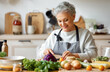 Happy mature woman preparing healthy salad in kitchen