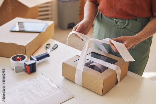 Close-up of woman decorating cardboard box with ribbon at the table before deliv Fototapet