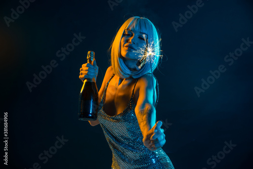 Woman In Dress With Sparkler And Champagne Standing Against Black Background - 381684906