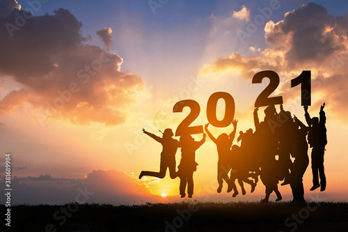 Obraz Silhouette of Business teamwork hands up and jump to the beautiful golden sky from text 2021 background .The concept of business sucess,victory,achieve target goal,busness growth. - fototapety do salonu