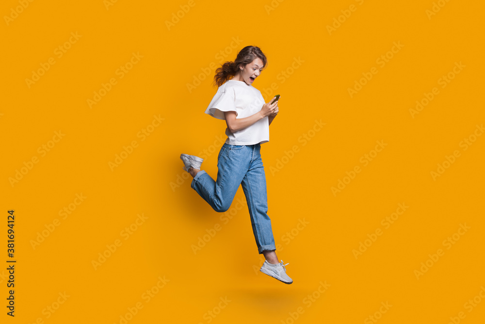 Fototapeta Emotional caucasian blonde woman running and jumping on a yellow studio wall while chatting on mobile and promoting something