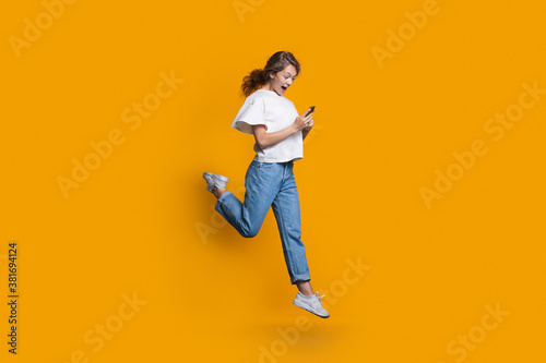 Emotional caucasian blonde woman running and jumping on a yellow studio wall while chatting on mobile and promoting something