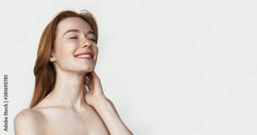 Fototapeta Ginger lady with freckles is wearing anti aging eye patches posing on white studio wall with naked shoulders advertising something