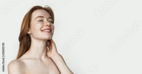Obraz Ginger lady with freckles is wearing anti aging eye patches posing on white studio wall with naked shoulders advertising something - fototapety do salonu