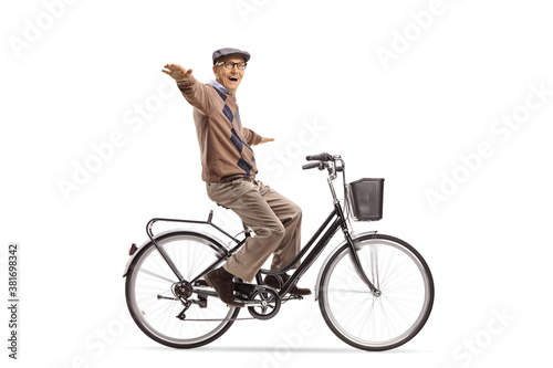 Fotografija Happy elderly man riding a bicycle and spreading arms