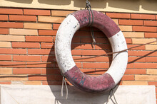 Old Ring Life Buoy, Also Known As A Kisby Ring Or Perry Buoy, Hanging From A Brick Wall