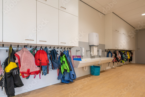 Photo ARNHE, NETHERLANDS - Aug 28, 2020: Cloakroom with coats and backpacks in a schoo