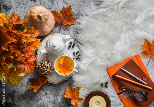 Fotografia, Obraz Sea buckthorn tea, maple leaves, fluffy carpet, books, pumpkin - cozy still life