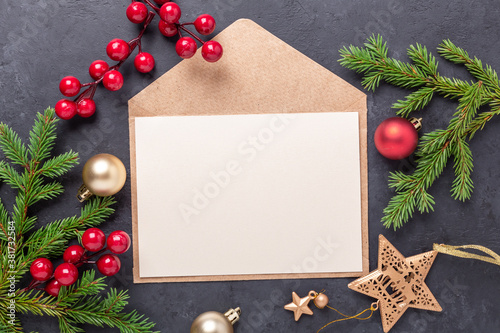 Christmas greeting card with fir tree branch, gifts, holly and envelope. Dark stone background Top view