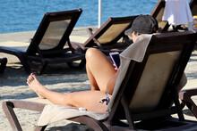 Woman In Bikini Sitting On Dec...