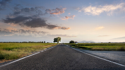 Panoramic of a long empty asphalt road towards sunset sky. Empty copy space for Editor's content.