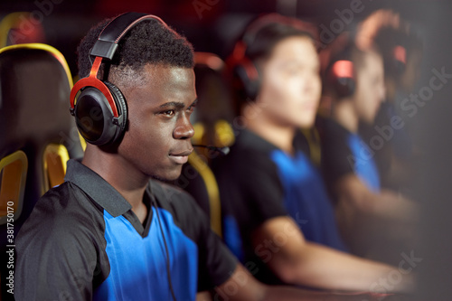 Obraz na plátně Side view of african male cybersport male gamer wearing headphones playing video