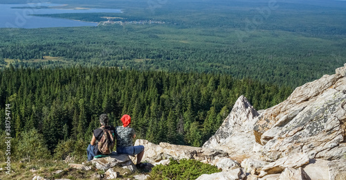 Back shot of middle age couple in love sitting down in the mountains on edge of cliff, admiring the view Canvas Print