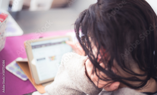 Photo Soft blurred concept of internet addiction - young woman with messy hair on tablet