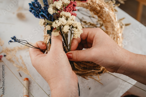 Fotografering Girl making floral door wreath using colorful dry summer flowers and plants
