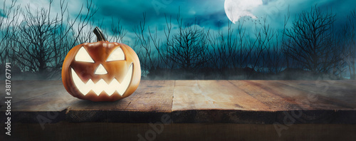 Jack O 'Lanterns with glowing eyes on a wooden table on spooky Halloween night u Canvas