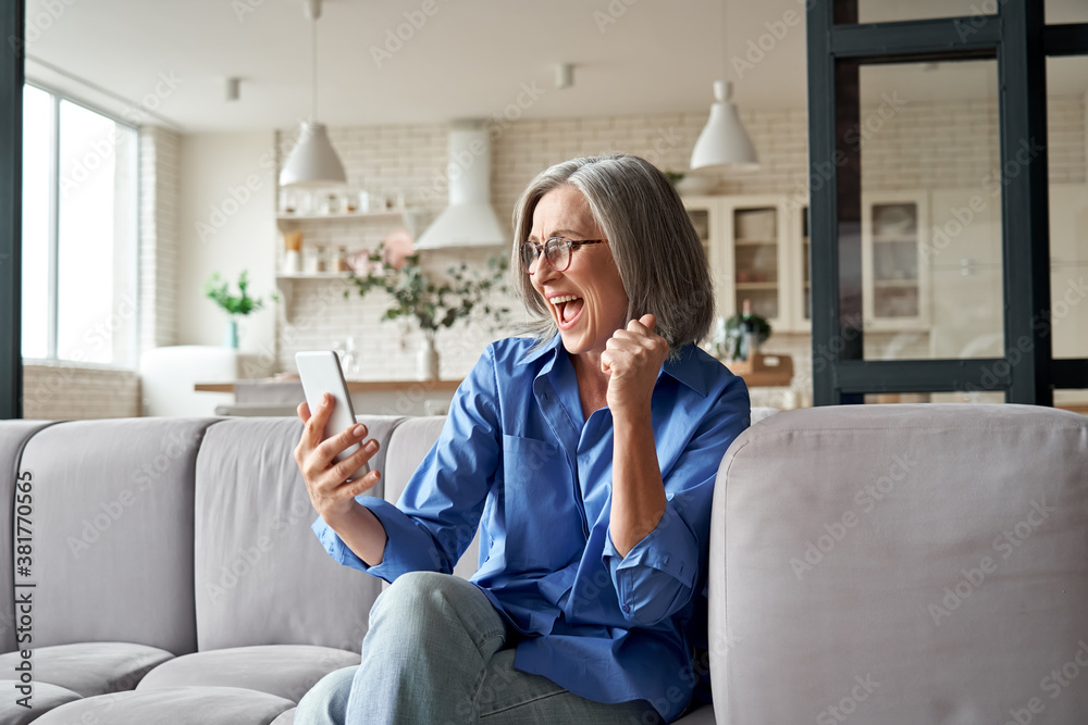 Fototapeta Excited happy mature old 60s woman customer winner holding smartphone using mobile app winning online lottery bid, celebrating success, receiving gift voucher on cell phone sitting on couch at home.