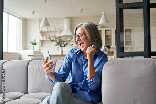 Obraz Excited happy mature old 60s woman customer winner holding smartphone using mobile app winning online lottery bid, celebrating success, receiving gift voucher on cell phone sitting on couch at home. - fototapety do salonu