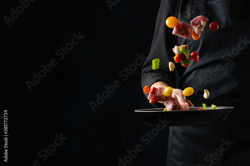 Fotografiet The chef in black apron throwing the fresh meat, beef or pork, mixed with vegetables, on dark background