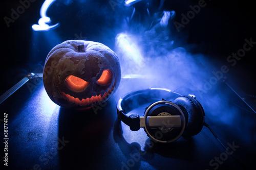 Fototapeta Halloween pumpkin on a dj table with headphones on dark background with copy space