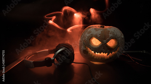 Fotografie, Obraz Halloween pumpkin on a dj table with headphones on dark background with copy space