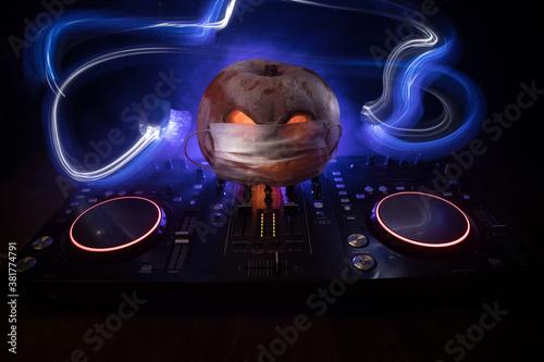 Carta da parati Halloween pumpkin on a dj table with headphones on dark background with copy space