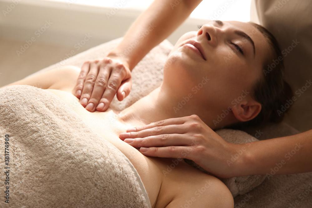 Fototapeta Young woman receiving body massage in spa salon