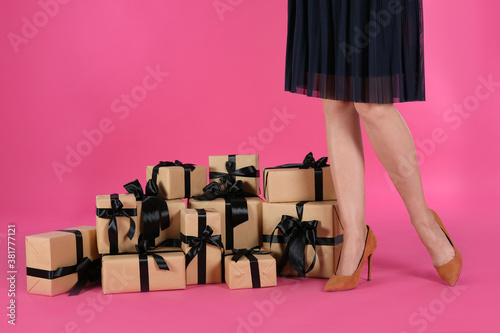Fototapeta Woman and gift boxes on pink background, closeup. Black Friday Sale obraz