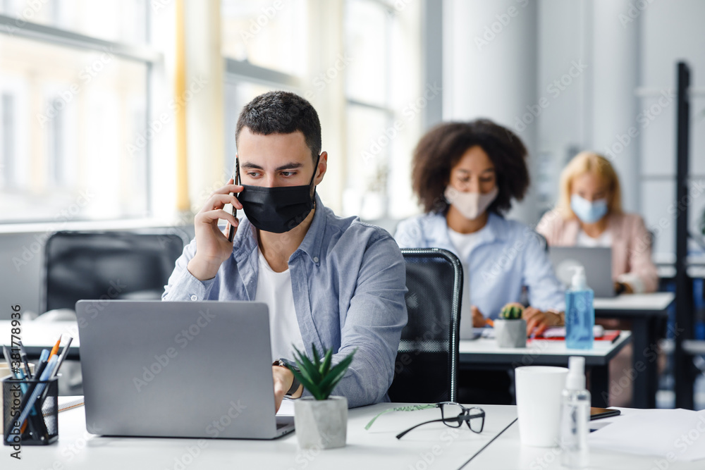 Fototapeta Customer consultation by phone remotely at returning to work after quarantine. Millennial man in protective mask with smartphone looks at laptop at workplace