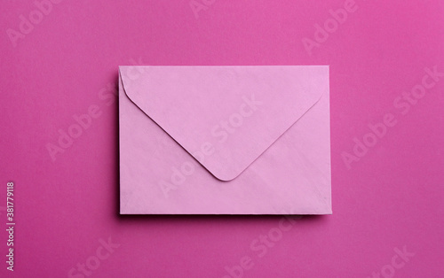 Leinwand Poster Pink paper envelope on purple background, top view
