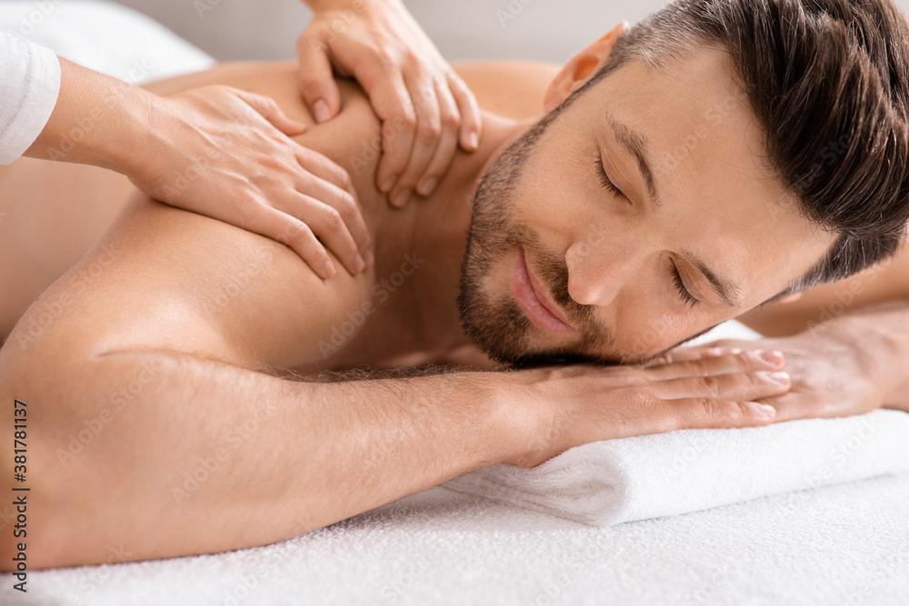 Fototapeta Closeup of relaxed man having body massage at spa