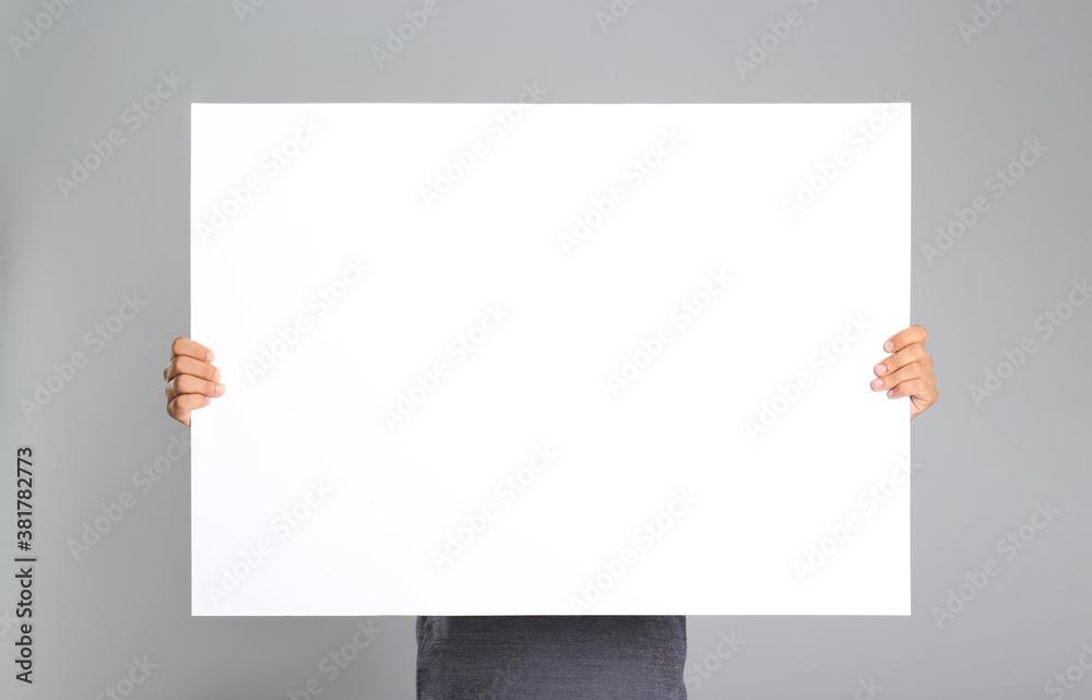 Fototapeta Man holding white blank poster on grey background. Mockup for design
