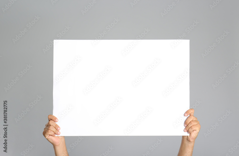 Fototapeta Man holding white blank poster on grey background, closeup. Mockup for design