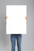 Man Holding White Blank Poster...