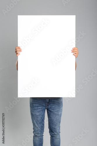 Fotografia Man holding white blank poster on grey background