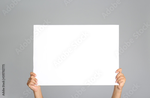 Man holding white blank poster on grey background, closeup Canvas Print