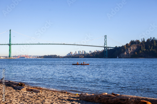 Платно Two people enjoy a sunny day canoe ride out of Ambleside Beach, West Vancouver,