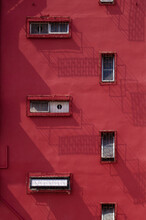 A Bright Red Wall. Exterior Facade Of Red Historical House With Apartments ,  Urban Vintage Background