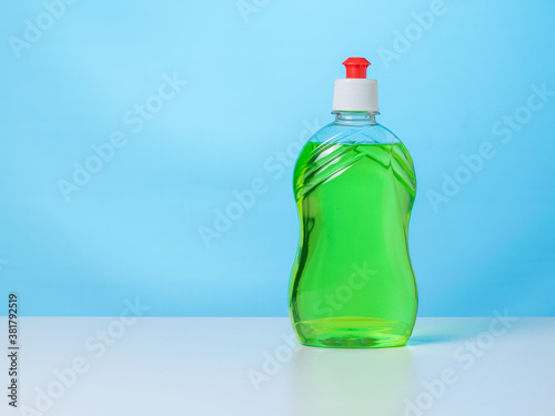 Obraz na plátně A bottle of green cleaning gel on a white table on a blue background