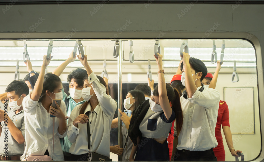 Fototapeta Many people on the train wear anti-virus masks and travel during rush hours.