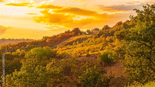 Fototapeta Na zdjęciu widzimy przepiękny zachód słońca rzucający swoje ostatnie promienie na to zbocze góry dając przepiękny widok tak jakby było namalowane na płótnie. obraz