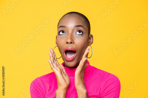 Fototapeta Close up portrait of surprised young African American woman looking upward with hands cupped around mouth isolated on studio yellow background obraz