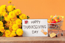 Thanksgiving Autumn Composition With Yellow Flower And Shopping Cart With Pumpkins On Orange Background.