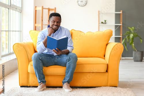 African-American man reading book at home Tapéta, Fotótapéta