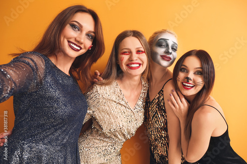 Vászonkép Friends in Halloween costumes taking selfie on color background