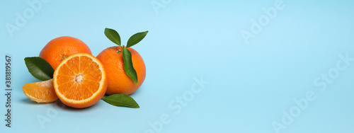 Ripe sweet mandarins on blue background, space for text