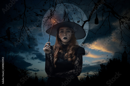 Halloween witch holding magic wand standing over cross, church, crow, bat, birds, dead tree, full moon and sunset sky, Halloween mystery concept