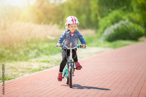 Cure little girl riding on bicycle Fototapeta