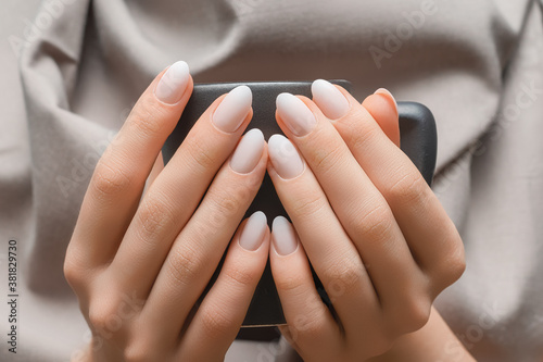 Female hands with white nail design. White nail polish manicure. Female hands holding grey coffee cup